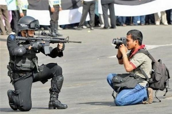 Một phóng viên tác nghiệp ngay trước họng súng của một cảnh sát chống bạo động. (Ảnh: internet)
