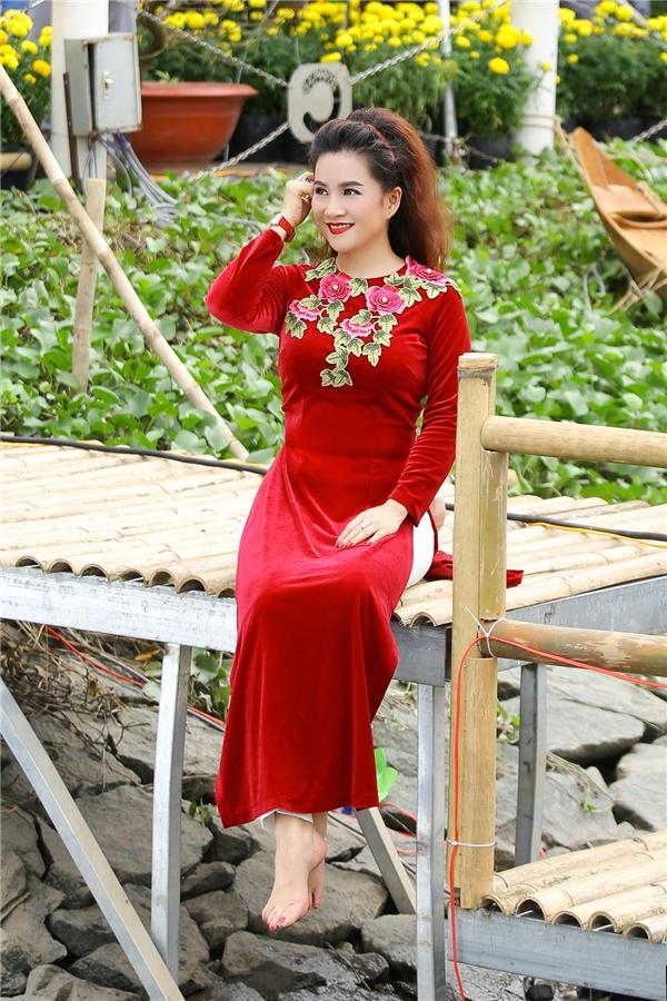 Anh Thơ tươi tắn, rạng rỡ với thiết kế màu đỏ sang trọng trên nền chất liệu nhung kết hợp họa tiết hoa to bản ở phần cổ tròn.