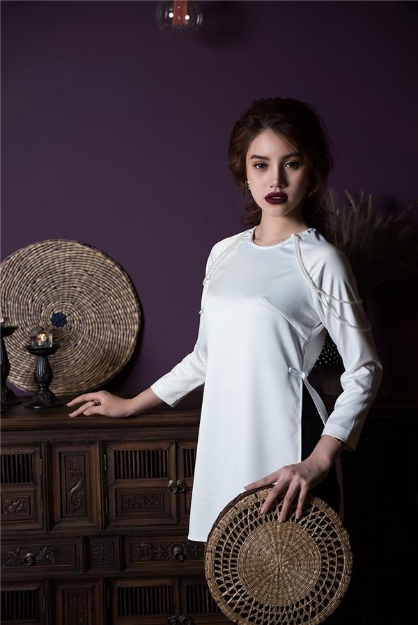 Sắc trắng, đen tương phản với phom áo ngắn giúp Jolie Nguyễn trông trẻ trung hơn. Phần áo truyền thống được cách điệu với chi tiết ngọc trai đính kết đối xứng ở phần cầu vai.