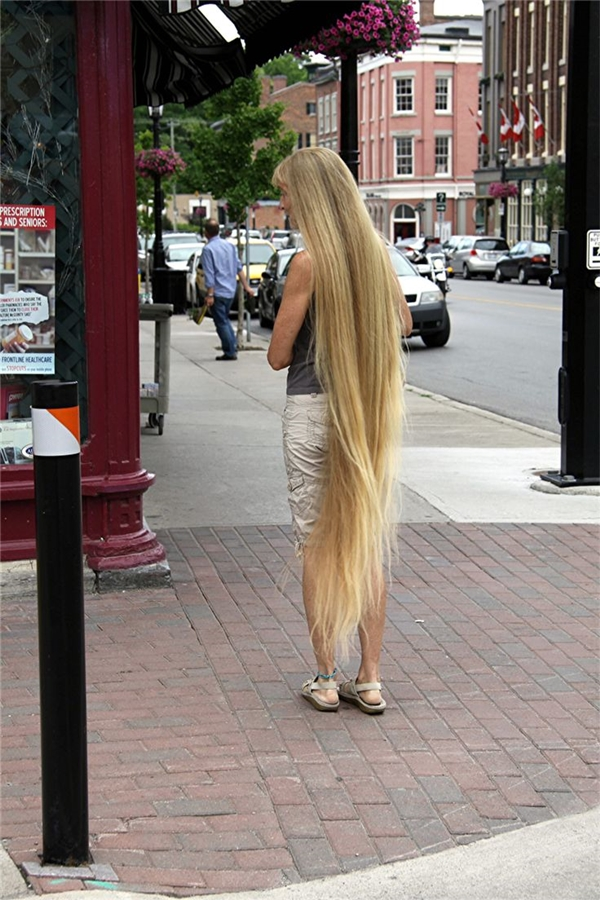 Tóc vàng óng ả, dài thướt tha dường như không hợp với áo thun ba lỗ và quần đùi, dép cao su nhỉ?