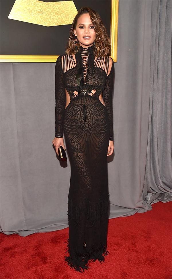 Bộ váy của Chrissy Teigen nhã nhặn với bộ váy đen trên nền chất liệu ren có những khoảng hở được bố trí tinh tế.