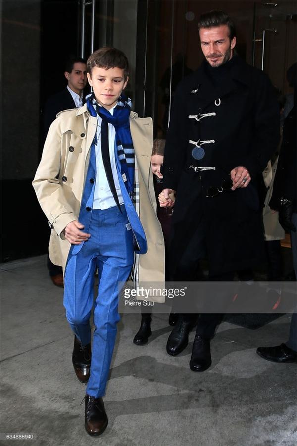 """Romeo Beckham """"ra dáng"""" khi diện chiếc suit màu xanh kết hợp với trench coat và khăn quàng của Burberry."""
