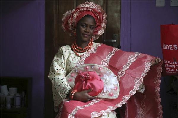 Váy cưới của cô dâu người Nigeria thường rất nổi bật với chất liệu ren sáng màu và họa tiết cầu kỳ. Họ đội một chiếc mũ và đeo một chuỗi hạt có màu tương tự.