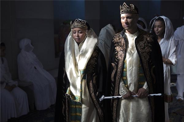 Trang phục của cô dâu và chú rể người Eritrea gồm có một chiếc mũ miện bằng nhung đen và một tấm váy màu tím thêu họa tiết vàng. Trang phục của cả hai phải hòa hợp và bổ sung cho nhau.