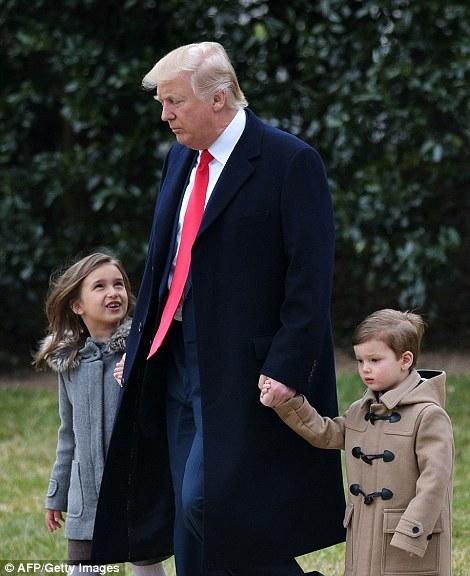 Ông Trump dắt tay hai cháu ngoại tại bãi cỏ bên ngoài Nhà Trắng.