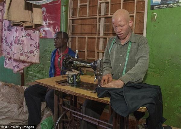 Thợ may Henry Bauti (bên phải) làm việc tại Trung tâm Thương mại Mitundu trong một khu dân cư ở Lilongwe.